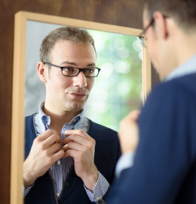 Portrait of young man with glasses getting ready, dressing up and looking at mirror